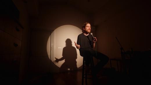 Bo Burnham sitzt im Dunkeln auf einem Stuhl und wird von einem Spotlight angestrahlt.