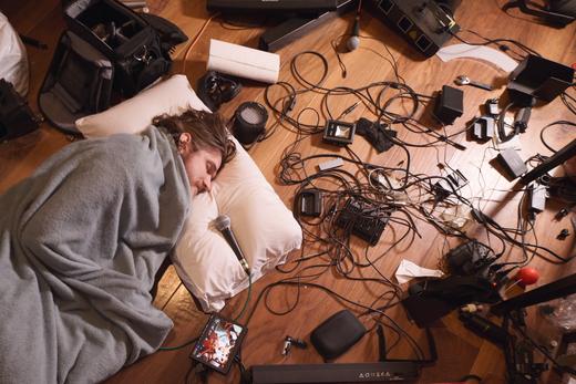 Bo Burnham liegt inmitten von unordentlichem Video-Equipment eingewickelt in eine Decke und spricht in ein Mikrofon.