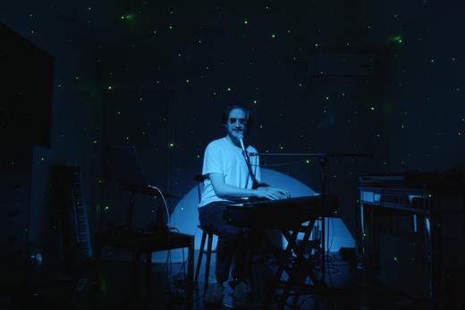 Bo Burnham sitzt mit Lichteffekten in einem dunklen Raum und wird durch ein Spotlight angestrahlt.