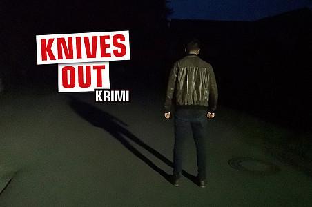 """Mann auf dunkler Straße mit Schriftzug """"Knives Out"""""""