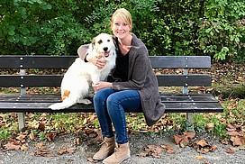 Mara sitzt mit einem Hund auf einer Bank